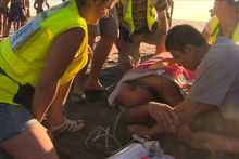 Surf rescue attend to a group of people on the beach at Piha after they had to be pulled from dangerous conditions. Photo / Piha Rescue