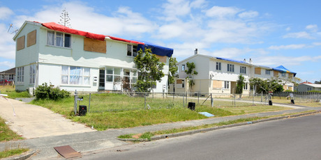 In Wallingford Way, Hobsonville, hundreds of windows remain boarded up and roofs are covered with tarpaulins or tied down with ropes.  Photo / Chris Gorman