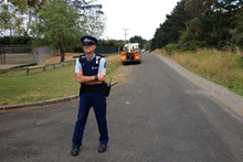 A police officer guards the entrance to where a body was found in Kingseat. Photo / Brett Phibbs