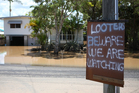 A sign is put up in East Bundaberg after reports of looters as parts of southern Queensland experiences record flooding. Photo / Getty Images
