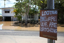 A sign is put up in East Bundaberg after reports of looters as parts of southern Queensland expe