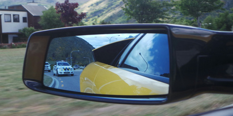 A police car follows the Lamborghini. Photo / Louise Taylor