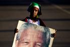 Lehlogonolo Nkosi, 7, holds a portrait of Nelson Mandela. Photo / AP
