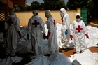 Red Cross employees stand amid dozens of bodies at the morgue in Bangui, Central African Republic. Photo / AP