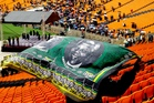 A man covers himself from the rain as he arrives for the memorial service for former South African president Nelson Mandela at the FNB Stadium in Soweto, near Johannesburg. Photo /AP