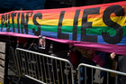 Protestors hold a rainbow banner banner reading 'Don't Buy Putin's Lies' during the U.S. Olympic Committee's Road to Sochi 100 Day Countdown event. Photo / AP