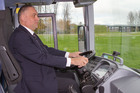 A driver poses behind the wheel of a bus outfitted with a fatigue monitoring system. Photo / Supplied