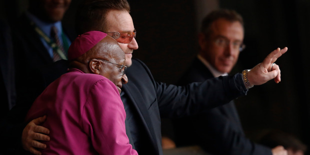 Retired Anglican Archbishop Desmond Tutu and musician Bono wave to mourners during the memorial service for former South African president Nelson Mandela. Photo / AP