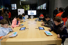 Children build code using iPads at a workshop in California this month. Apple has a lot of happy customers, and according to a labour advocacy group, conditions for its Chinese workers are improving. Photo / AP