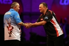 Sixteen-times world champion Phil Taylor, left, is congratulated by New Zealander Rob Szabo. Photo / Getty Images