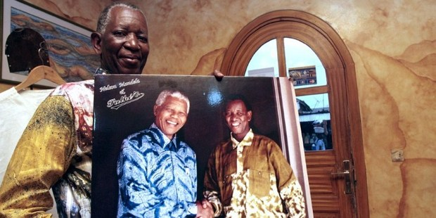 Pathe Ouedraogo holds a photo of Nelson Mandela shaking hands with him. Photo / AFP