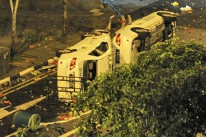 Two police cars flipped to their sides remain in the street after a riot broke out in Singapore. Photo / AFP