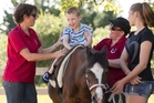 Children such as Jordan, who has cerebral palsy, enjoy their time riding. He is helped by Alison Green (left), Alison Daldy and Molly Green. Photo / Greg Bowker