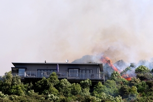 Flames close to a home in Tumbledown Bay Rd, Port Underwood, near Picton. Photo / Andrew Lucas