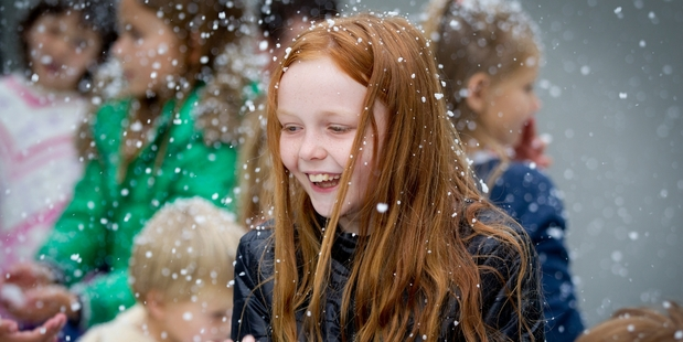 Ashley Hook, 10, has the joy of Christmas snow without the cold as the snow machine works its magic at the Franklin Rd street of lights in Freemans Bay, Auckland. Photo / Sarah Ivey