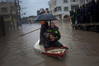 Palestinian rescue members evacuate a cat following heavy rains in Gaza City. Photo / AP