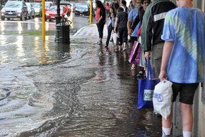 George St or George River? Shoppers on Dunedin's main street try to keep high and dry yesterday. Photo / ODT