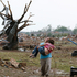 A woman carries her child through a field in Moore, Oklahoma. Photo / AP
