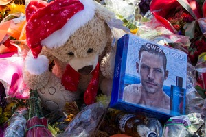 Flowers and messages are left at a memorial rally and car cruise in Valencia, California to remember actor Paul Walker and his friend Roger Rodas. Photo / AP