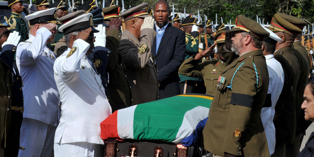 Military officers salute as Mandela's grandson Mandla Mandela watches over the casket as it arrives at the Mandela residence in Qunu, South Africa. Photo / AP