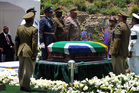 Nelson Mandela's grandson Mandla Mandela, left, watches as military soldiers stand at attention over former South African President Madela's casket before his burial. Photo / AP