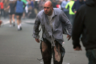 Boston Marathon bombing victim James Costello staggers away from the blast in torn clothing. Photo / Kenshin Okubo / AP