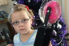 Seven-year-old Tegan Gadsby, of Masterton, with her wrecked scooter which many people have offered to replace.