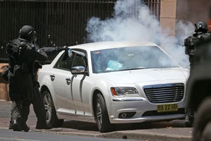 A police officer sprays tear gas into the vehicle to end the protest. Photo / AP