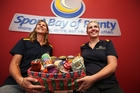 Jen Riley and Holly Cutbush of Sport Bay of Plenty with their donation to the Tauranga Foodbank. Photo / Joel Ford