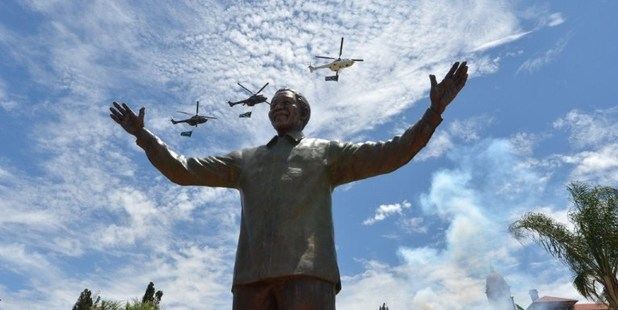 Helicopters carrying the South African flag fly over a 9-metre bronze statue of South African former president Nelson Mandela. Photo / AFP