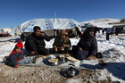 Syrian refugees eat their lunch outside their tent at a refugee camp in the eastern Lebanese border town of Arsal, Lebanon. Photo / AP