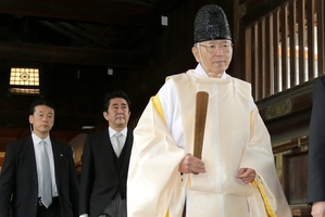 Shinzo Abe (centre) follows a Shinto priest to the shrine. Abe says the visit was an anti-war gesture. Photo / AP