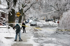 People clear snow from footpaths on a closed-off street in Toronto after an ice storm knocked down trees and powerlines. Photo / AP