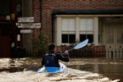 A man canoes along the town centre streets submerged under floodwater checking on people in Yalding, England. Photo / Getty Images