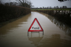 A council sign sits in flood water on a road near Lingfield in England. Photo / Getty Images