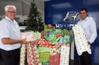 CHRISTMAS CHEER: Eastwood Motor Group owner Mike Allan (left) and sales manager Gary Allan with the haul of presents the community has given for children. PHOTO/LYNDA FERINGA