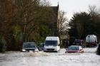 A car navigates a flooded road near Reigate, England. Photo / AP