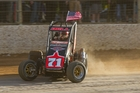 Chris Bell flies the flag for the United States during the feature midget car race at Western Springs. Photo / James Selwyn