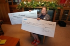 MAKING A DIFFERENCE: Suzie Adamson, general manager Wairarapa Hospice, with two huge cheques for monies raised and donated to the hospice. PHOTO/LYNDA FERINGA