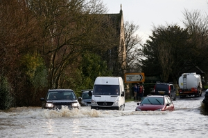 Torrential rain turned this road near Reigate in England into a river. Other areas of the country were also hit by flooding, and transport was disrupted. Photo / AP