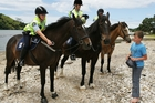 SADDLING UP: Braedyn McLachlan being offered a wristband by Constable Claire Carter at Pataua South yesterday as Whangarei police started patrolling the district's beaches on horseback. PHOTO/RON BURGIN