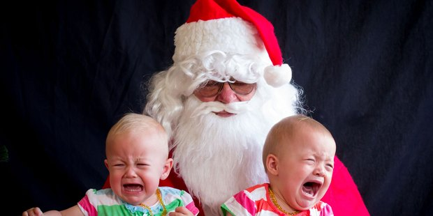 Don't worry girls, Christmas is nearly done with! Thirteen-month-old twins Eleanor, left, and Emily Williams not enjoying their time with Santa.