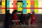 A woman talks to a salesperson in front of an advertisement for iPhones at Apple's retail store in Beijing Monday, Dec. 16, 2013. Photo / AP