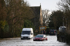 A van and a car stuck in a flooded road near Reigate, England. Photo / AP