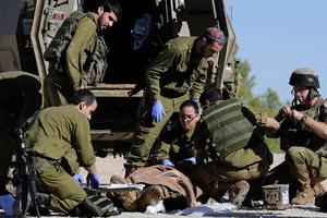 Israeli army paramedics treat a civilian shot near the Israel and Gaza border, Tuesday. Photo / AP