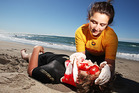 Alisha King performs first aid on Hamish Riegel during a mock rescue at Papamoa beach.