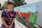 STREET SCENE: Jo Thomas was interviewed about her art work by Channel North in front of the broadband services cabinet she painted in Paramount Pde, Tikipunga. PHOTO/JOHN STONE