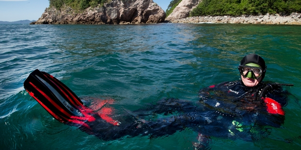 """Loading Darrell Bird, owner of Dive Zone Whitianga, relaxes in his """"office"""" in the marine reserve near Hahei Beach. Photo / Alan Gibson"""