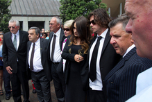 Family and friends pay their respects, as Sir Paul Holmes' coffin sits in the hearse, during his funeral at the Holy Trinity Cathedral, Parnell. Photo / Brett Phibbs