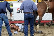 Cam Billing, of Te Awamutu, lies injured after being bucked into the back of a stall at the Outram Rodeo yesterday. Photo / Craig Baxter